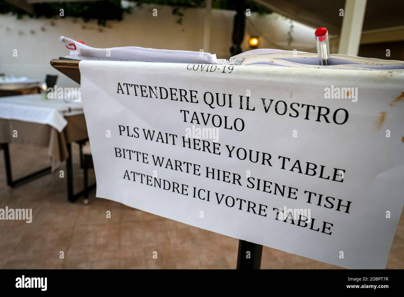 Restaurant sign informs guests to wait until seated in different languages, assuring social distancing regulations during the coronavirus pandemic. Stock Photo