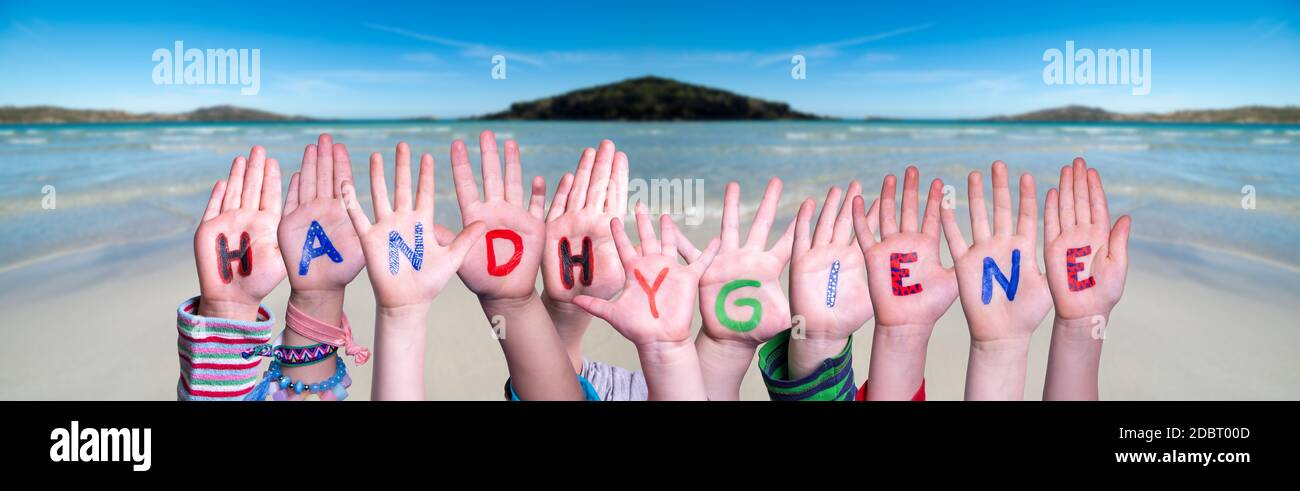 Kids Hands Holding Colorful German Word Handhygiene Means Hand Hygiene. Ocean And Beach As Background Stock Photo