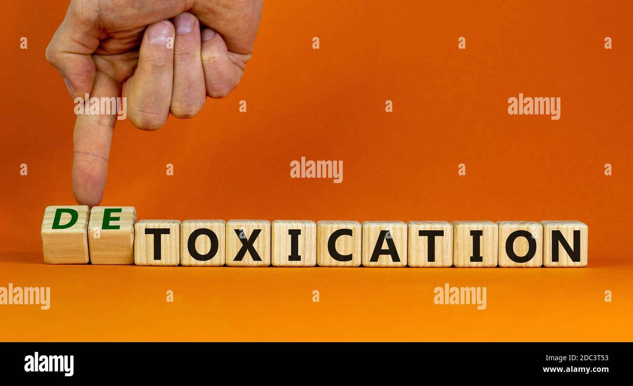 Hand flips cubes and changes the expression 'toxication' to 'detoxication'. Beautiful orange background. Healthy lifestyle concept. Copy space. Stock Photo