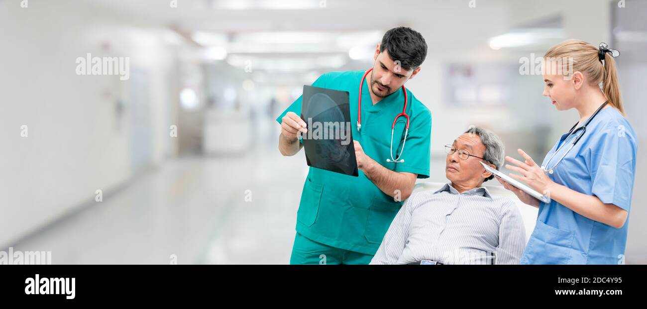 Surgeon showing xray film to senior patient looking at brain injuries with nurse standing beside the surgeon at the hospital room. Medical healthcare Stock Photo