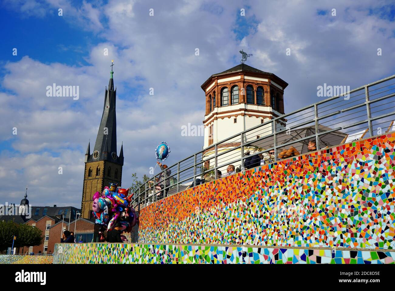 """""""Schlossturm"""" at Burgplatz with the colourful mosaic artwork """"Rivertime"""" by Hermann-Josef Kuhna and Lambertus church in the background. Stock Photo"""
