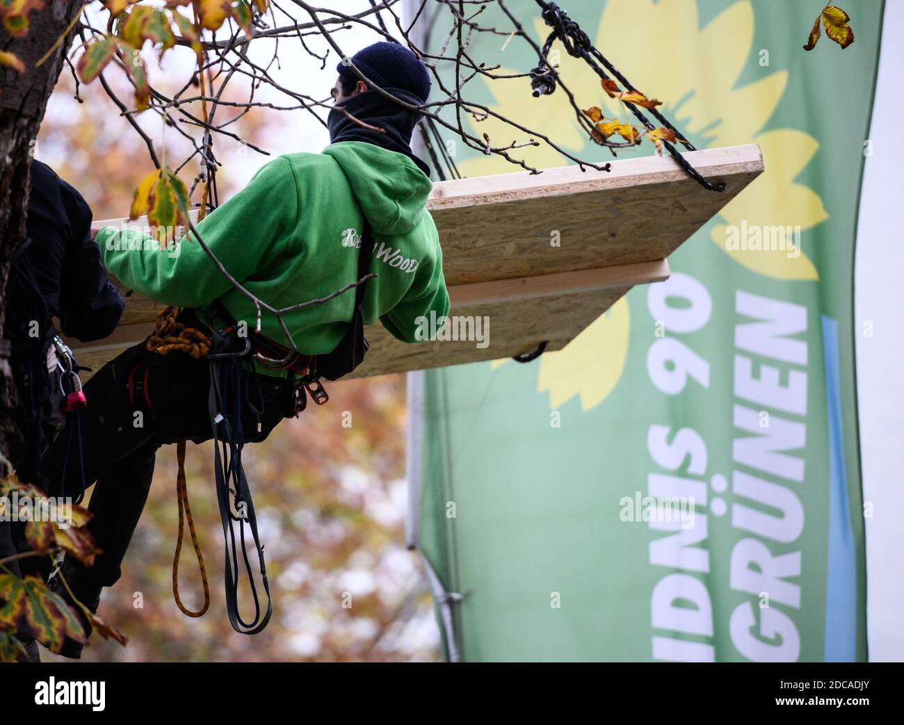 Wiesbaden, Germany. 20th Nov, 2020. An activist floats in front of the flag of Bündnis90/Die Grünen. Activists from Robin Wood, environmental and nature conservation organisation, have occupied two trees in front of the party headquarters of the Hessian Greens in the state capital. The organisation is protesting against the clearings in connection with the expansion of the A49 and wants to remind the Greens in Hesse of their political responsibility. Credit: Andreas Arnold/dpa/Alamy Live News Stock Photo