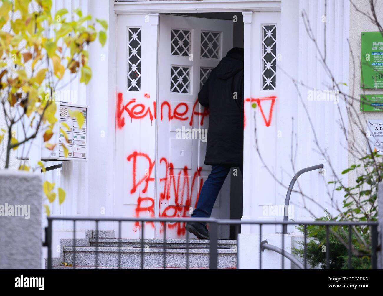 """Wiesbaden, Germany. 20th Nov, 2020. A man goes to the party headquarters of Bündnis90/The Greens in Hesse. The entrance door is smeared with the slogan """"No A49 Danni stays"""". Activists from Robin Wood, environmental and nature conservation organisation, have occupied two trees in front of the party headquarters of the Hessian Greens in the state capital. The organization is protesting against the clearings in connection with the expansion of the A49 and wants to remind the Greens in Hesse of their political responsibility. Credit: Andreas Arnold/dpa/Alamy Live News Stock Photo"""