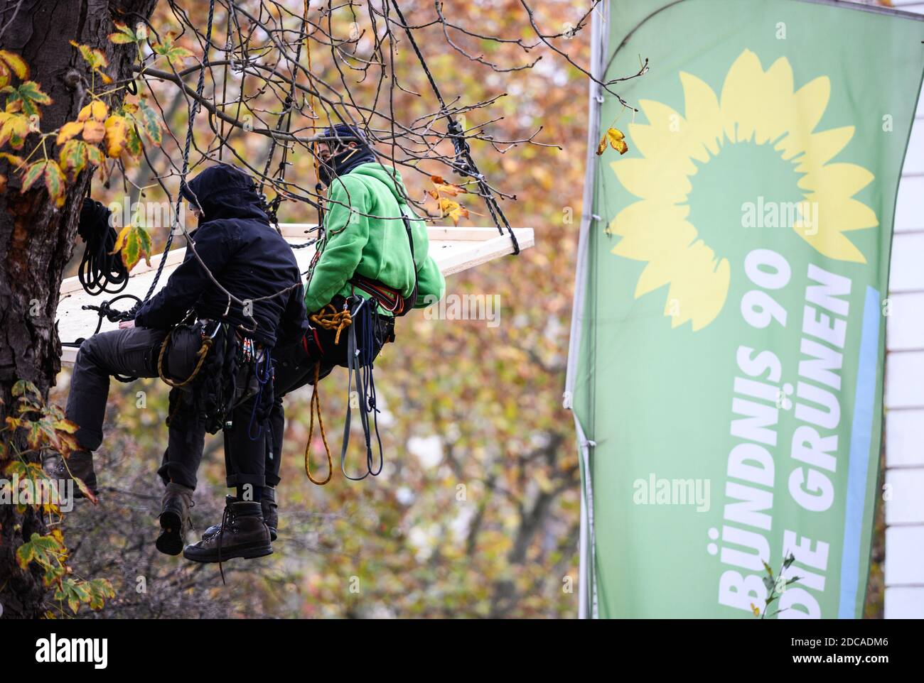 Wiesbaden, Germany. 20th Nov, 2020. Two activists hover in front of the flag of Bündnis90/Die Grünen. Activists from Robin Wood, environmental and nature conservation organisation, have occupied two trees in front of the party headquarters of the Hessian Greens in the state capital. The organisation is protesting against the clearings in connection with the expansion of the A49 and wants to remind the Greens in Hesse of their political responsibility. Credit: Andreas Arnold/dpa/Alamy Live News Stock Photo