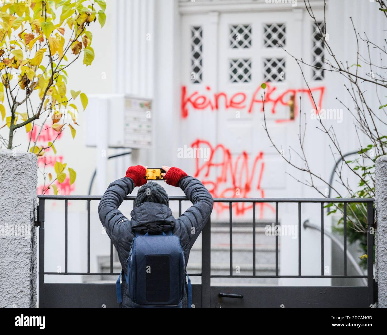 """Wiesbaden, Germany. 20th Nov, 2020. A woman takes a photo of the smeared entrance door """"No A49 Danni stays"""" to the party headquarters of Bündnis90/Die Grünen in Hesse. Activists from Robin Wood, environmental and nature conservation organisation, have occupied two trees in front of the party headquarters of the Hessian Greens in the state capital. The organisation is protesting against the clearings in connection with the expansion of the A49 and wants to remind the Greens in Hesse of their political responsibility. Credit: Andreas Arnold/dpa/Alamy Live News Stock Photo"""