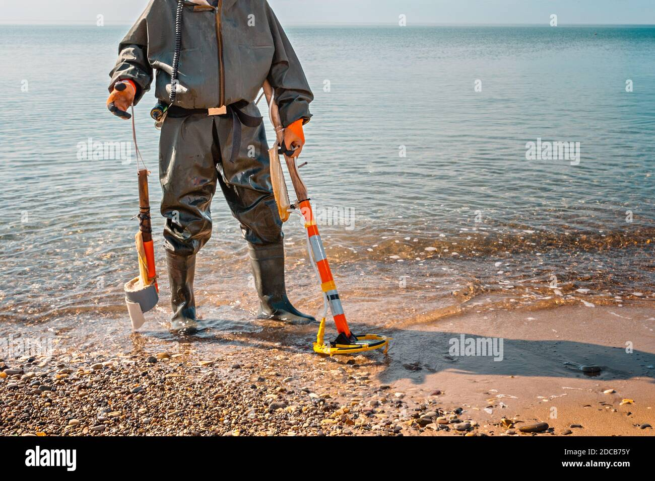 A man with a metal detector stands on the beach, ready for new archaeological finds. Sea on the background. Stock Photo