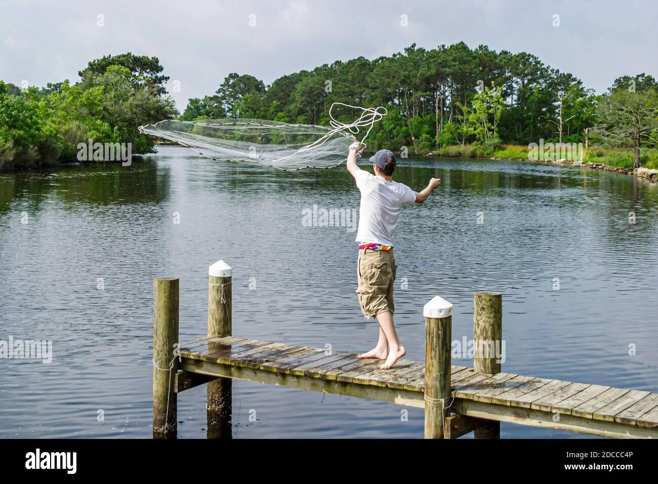 Louisiana St. Tammany Parish Slidell, Liberty Bayou, crabbing fishing man pier tossing net, Stock Photo