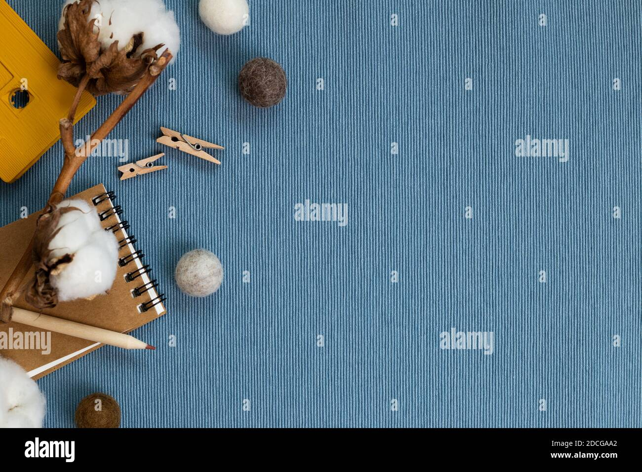 Winter concept. Notebook and pencil, cotton plant, cassette tape on blue fabric background. flat lay, top view, copy space. Work and study place Stock Photo