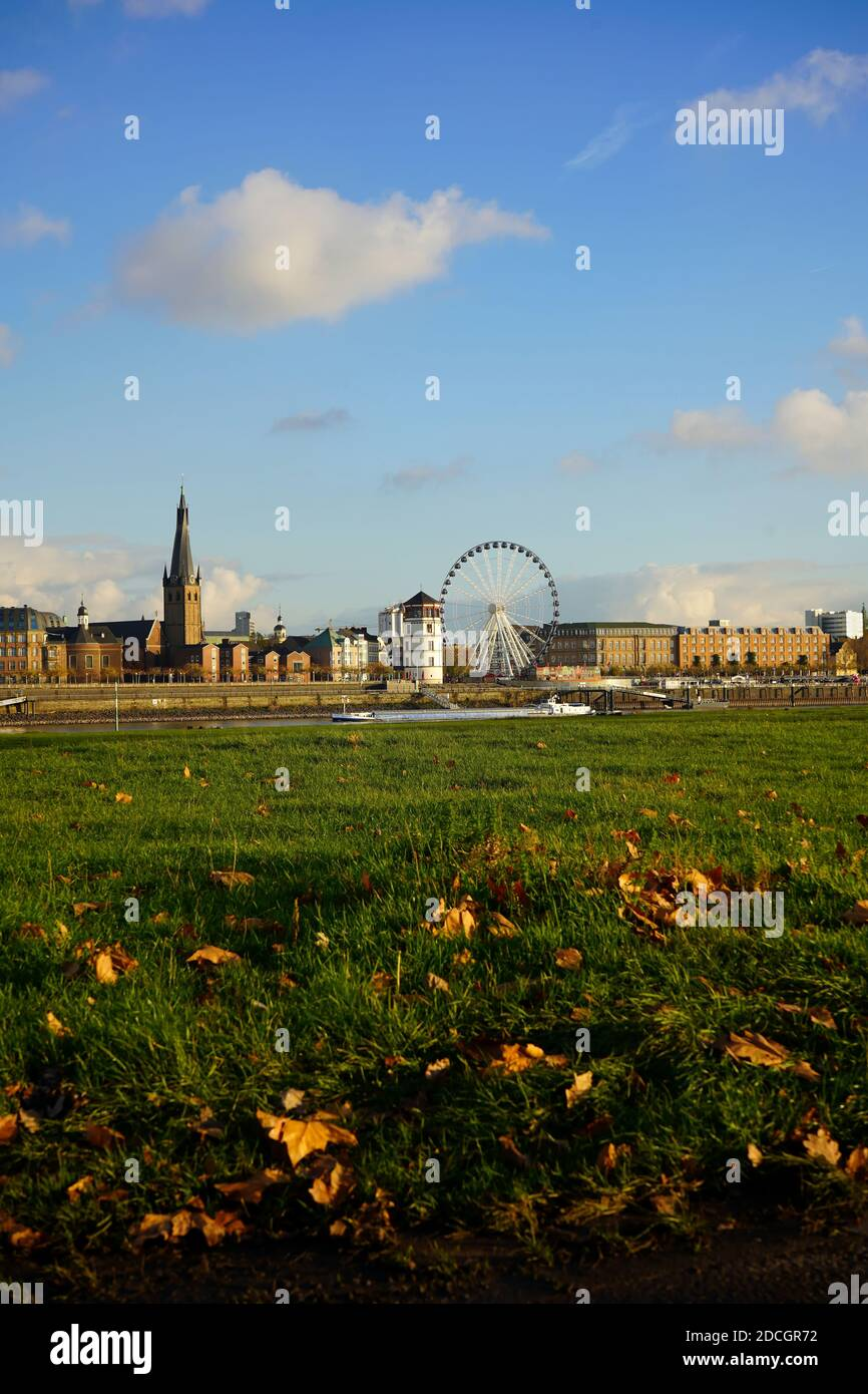 View across Rhine river from the district of Oberkassel, with white castle tower, Ferris wheel and a ship passing by. Sunny autumn day. Stock Photo