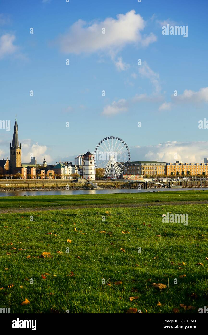 View across Rhine river with Lambertus Church, the historic castle tower and a Ferris wheel. Stock Photo