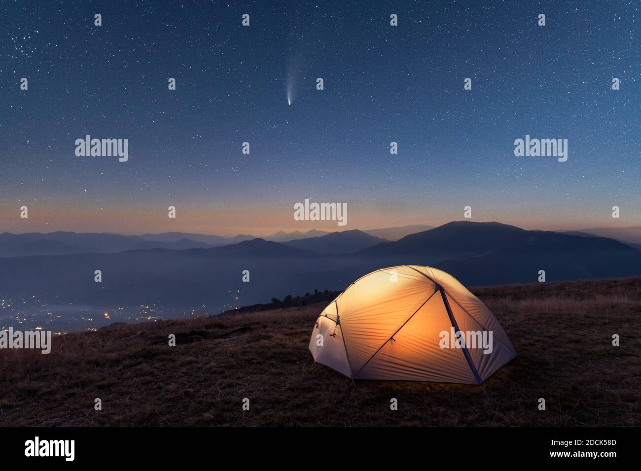 Green tent lighted from the inside by a flashlight against the backdrop of pine tree forest and glowind pink sky. Amazing snowy landscape. Tourists camp in winter mountains. Travel concept Stock Photo