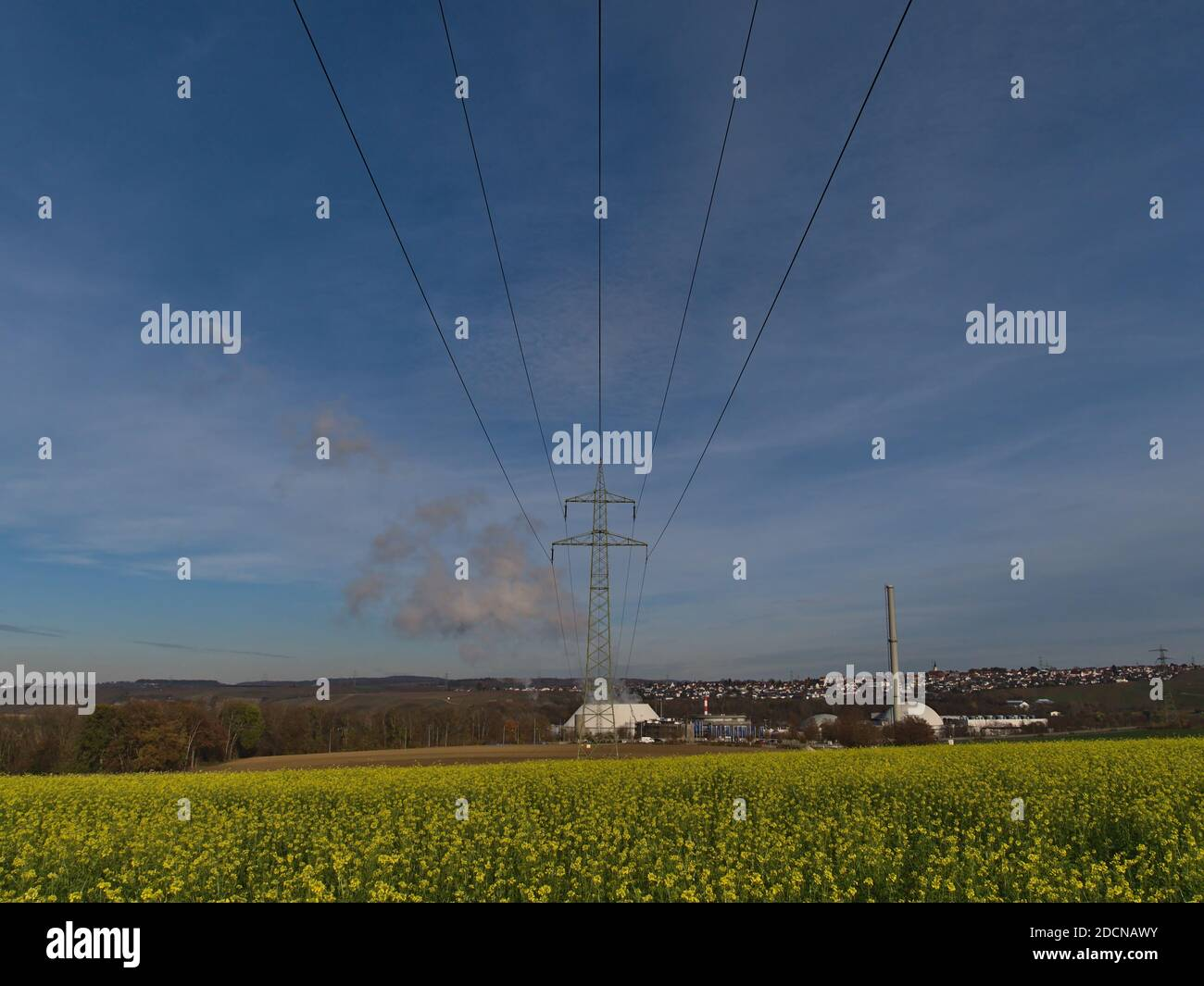 Bottom view of a power line with pylon connecting to nuclear power plant in Neckarwestheim, Germany with yellow blooming rapeseed flowers below. Stock Photo