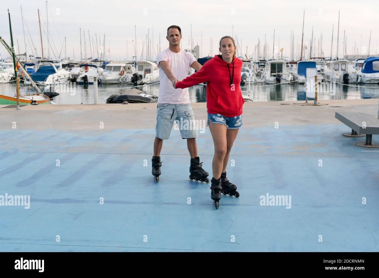Young happy couple roller skating in skate park next to the beautiful port in summer.Friendship sport and fitness lifestyle concept. Stock Photo