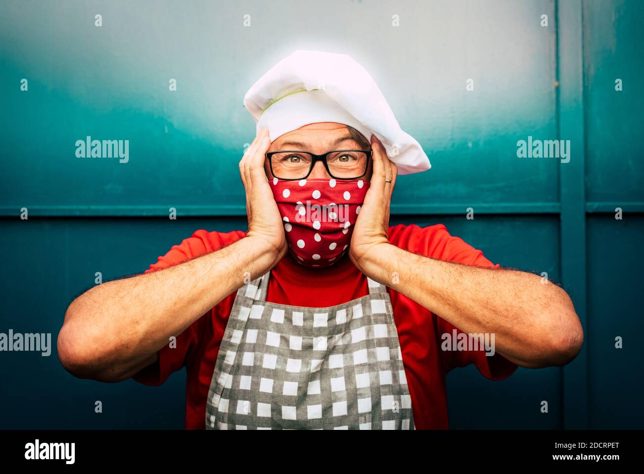 Portrait of smiling adult man with red santa hat and face mask for coronavirus covid-19 virus emergency - concept of christmas and holi Stock Photo