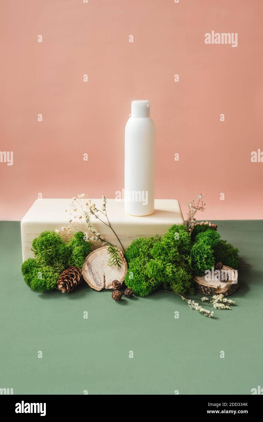 Blank white bottle on wooden brick with green moss. Natural organic cosmetics, alternative medicine, herbal essence, sustainable lifestyle concept. Fr Stock Photo