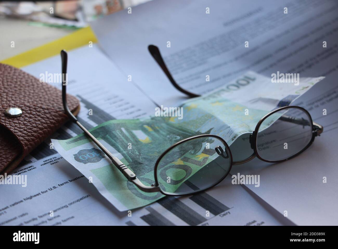 Brown leather wallet, 100 Euro banknote, glasses and financial report. Finance profit and loss analysis business concept Stock Photo