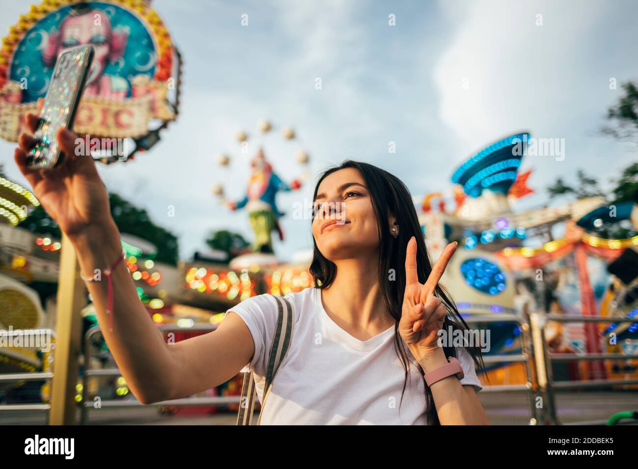 Beautiful young woman taking selfie through smart phone while gesturing peace sign at amusement park during summer Stock Photo
