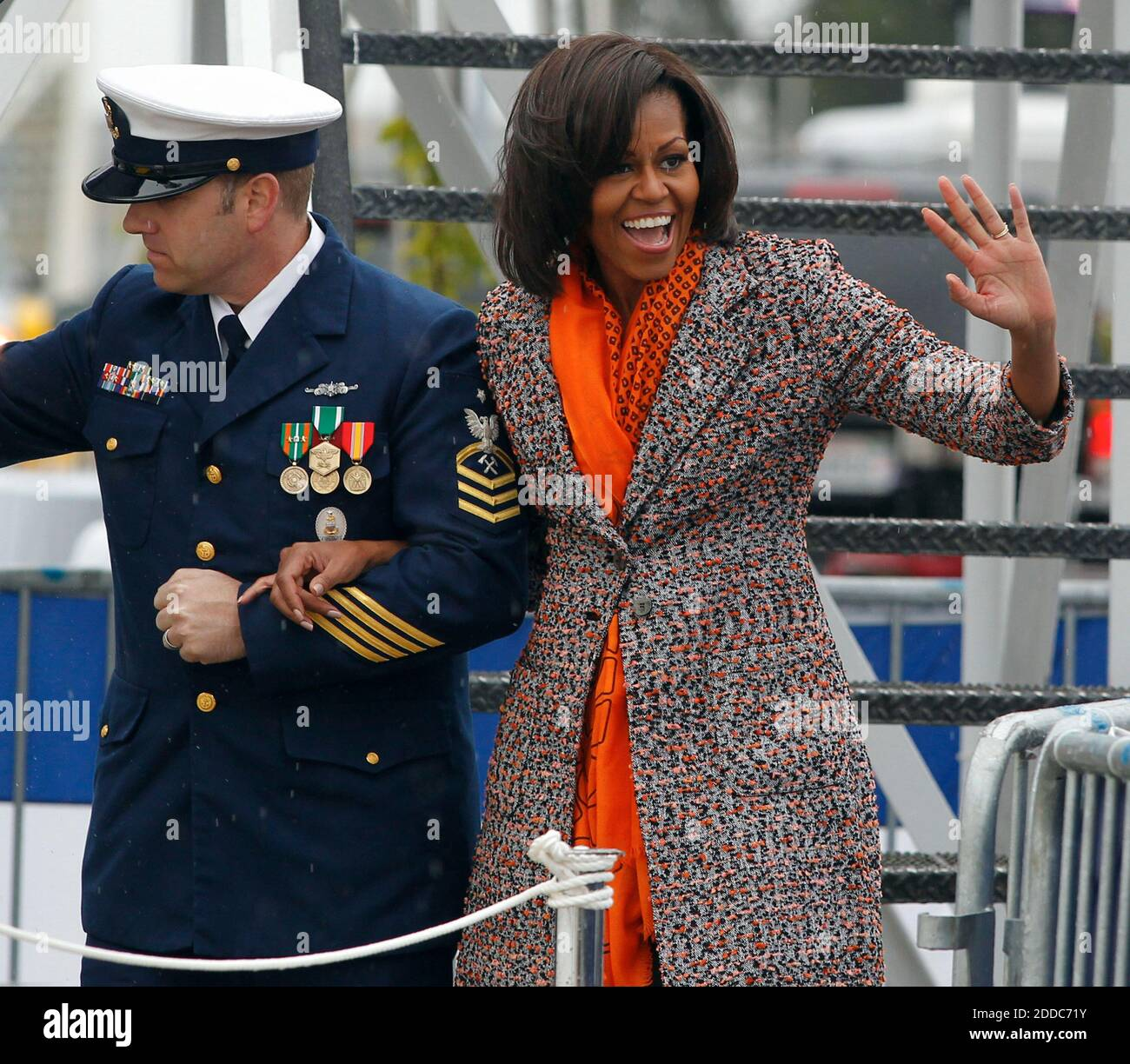 NO FILM, NO VIDEO, NO TV, NO DOCUMENTARY - First lady Michelle Obama, right, escorted by Coast Guard Senior Chief David Stephens, waves to members of the audience during her entrance from the Coast Guard Cutter Stratton for a ceremony on Coast Guard Island in Alameda, CA, USA ON March 31, 2012. The first lady made the trip to California to join in the commissioning ceremony placing the ship into active service. Photo by Anda Chu/Oakland Tribune/MCT/ABACAPRESS.COM Stock Photo