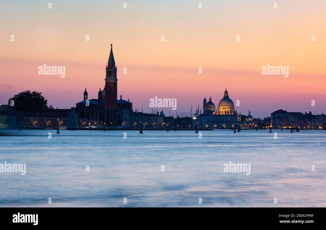 Italy, Veneto, Venice, Venetian waterfront at dusk with Santa Maria della Salute and San Giorgio Maggiore churches in background Stock Photo