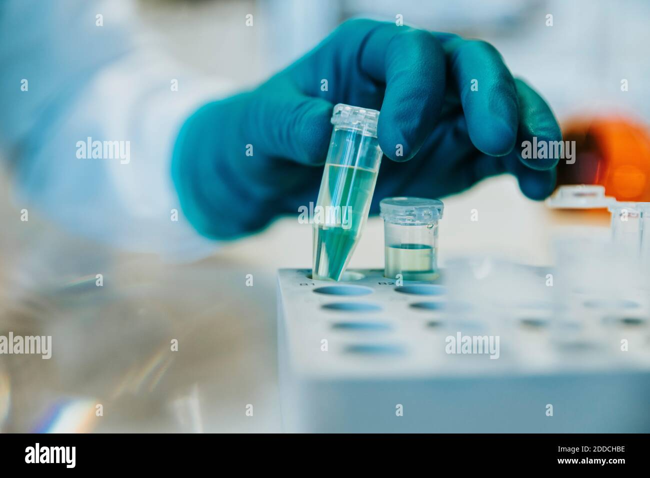 Woman wearing protective glove holding test tube while standing at laboratory Stock Photo