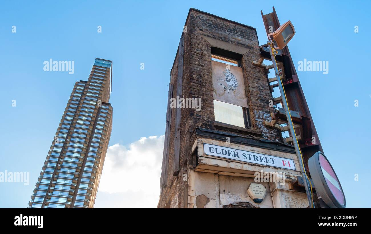 Contrast between a remnant of an old building and new high rise development in Spitalfields, London Stock Photo