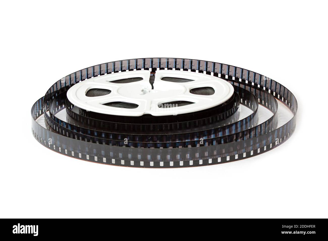 8mm film reel with film strips scattered around. Close-up image isolated on white background. Stock Photo