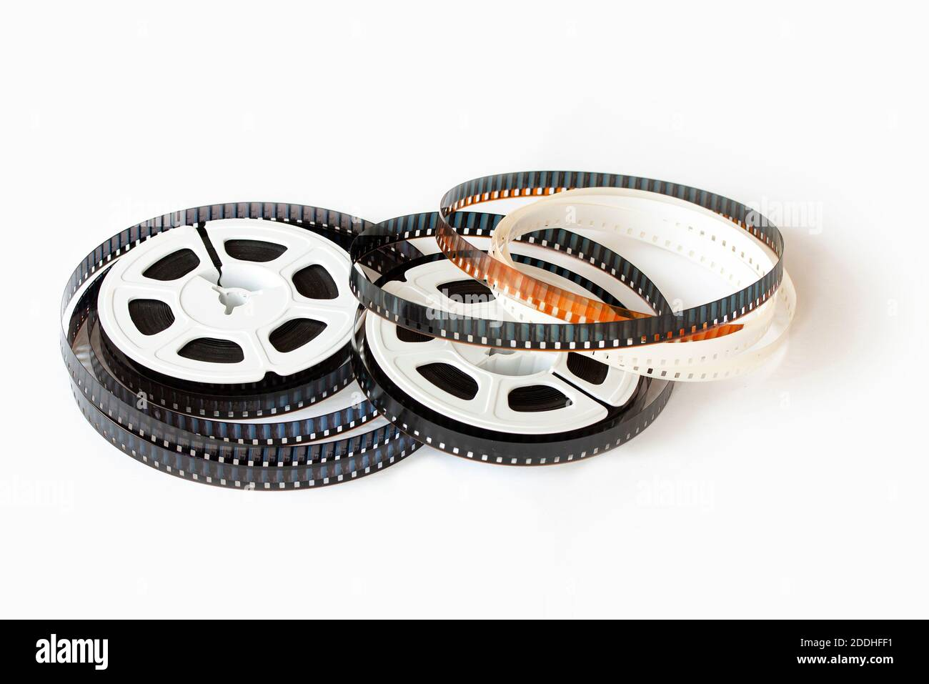 Two 8mm film reels with film strips scattered around. Studio shot. Close-up image isolated on white background. Stock Photo