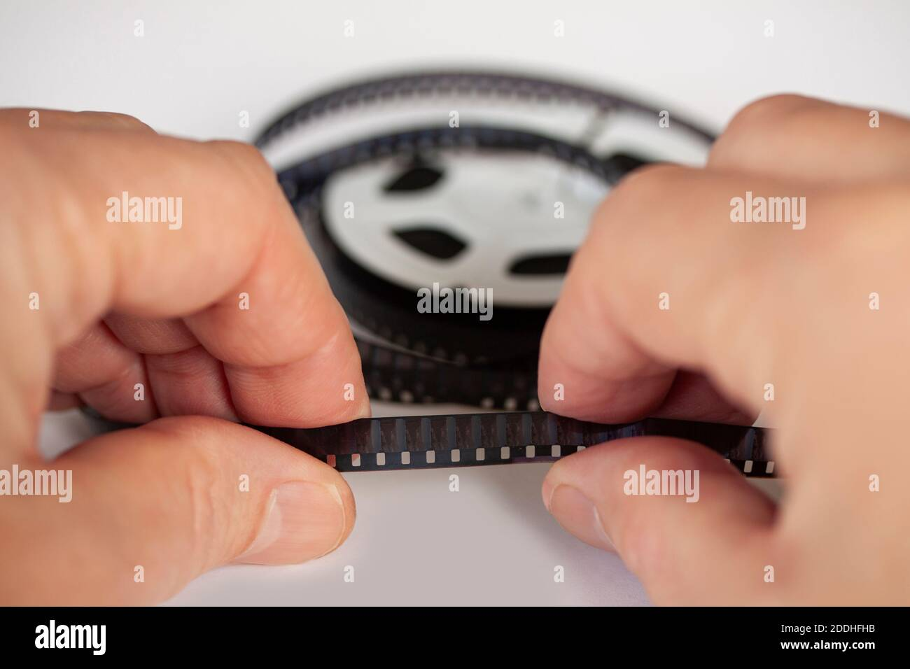 Hands holding a 8mm film strip with roll in background. Close up image with shallow depth of field. Stock Photo
