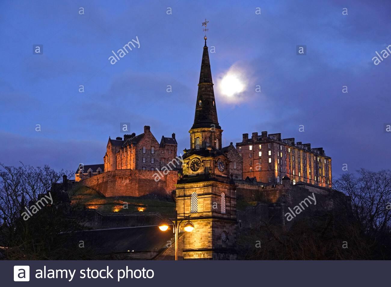 Edinburgh, Scotland, UK. 25th Nov 2020. Edinburgh city centre at dusk with an 81% waxing Gibbous Moon phase displaying over Edinburgh Castle and St Cuthbert's Church.   Credit: Craig Brown/Alamy Live News Stock Photo