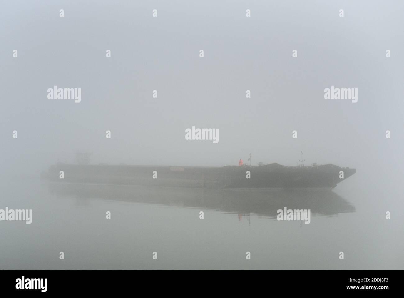 orange gekleider Mann auf einem Schiff welches aus dem Nebel auftaucht Stock Photo