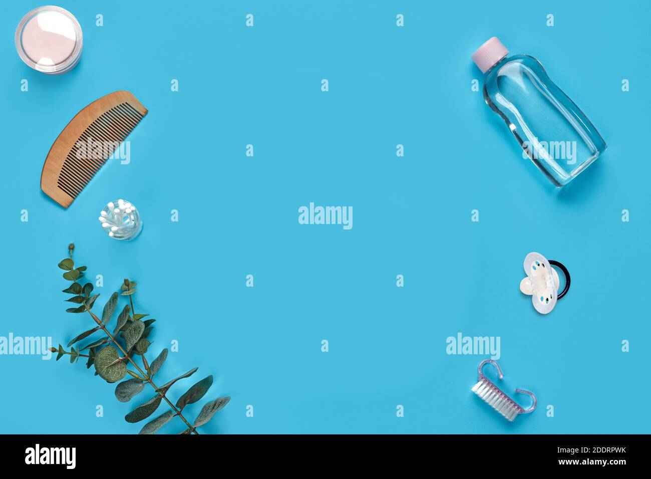 Wooden hair comb, cotton pads, pacifier, bottle with transparent liquid, cotton swabs, brush and green twig on blue background. Close up, copy space Stock Photo