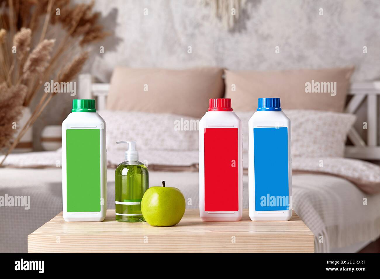 Three colorful plastic containers with detergents, pump bottle with soap and green apple on wooden bedside table in bedroom. Close up, copy space Stock Photo