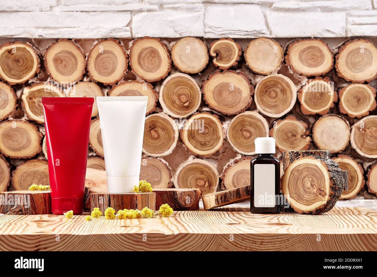 Two colorful cosmetic tubes and brown plastic bottle with branding area, small buds of blooming yellow flowers on wooden surface. Close up, copy space Stock Photo