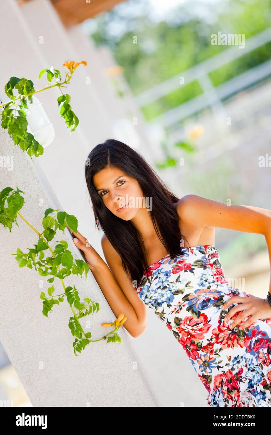 Teengirl standing behind leaves vegetation hand on hip pose posing Stock Photo