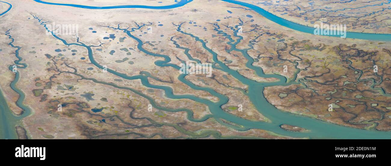 Meandering channels run through a beautiful estuary in Central California. Estuaries form when freshwater runoff meets and mixes with seawater. Stock Photo