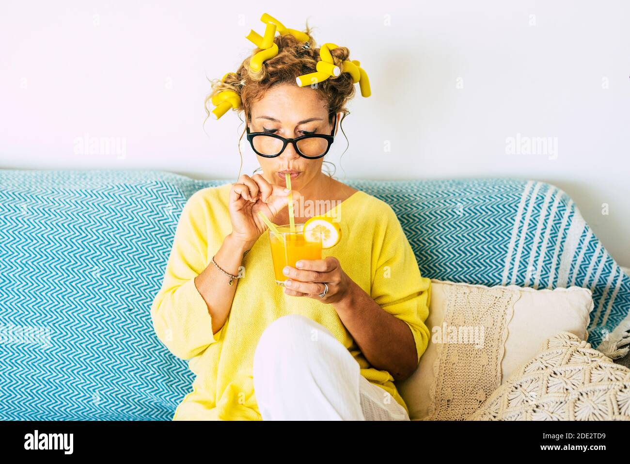 Yellow colors portrait of beautiful caucasian young adult woman drinking healthy orange juice at home with curlers and blue sofa in background - conce Stock Photo