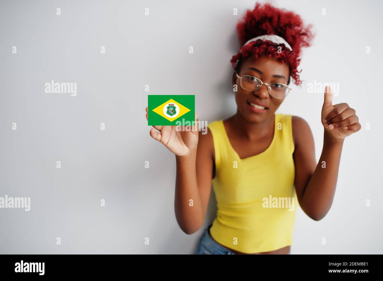 Brazilian woman with afro hair hold Ceara flag isolated on white background, show thumb up. States of Brazil concept. Stock Photo