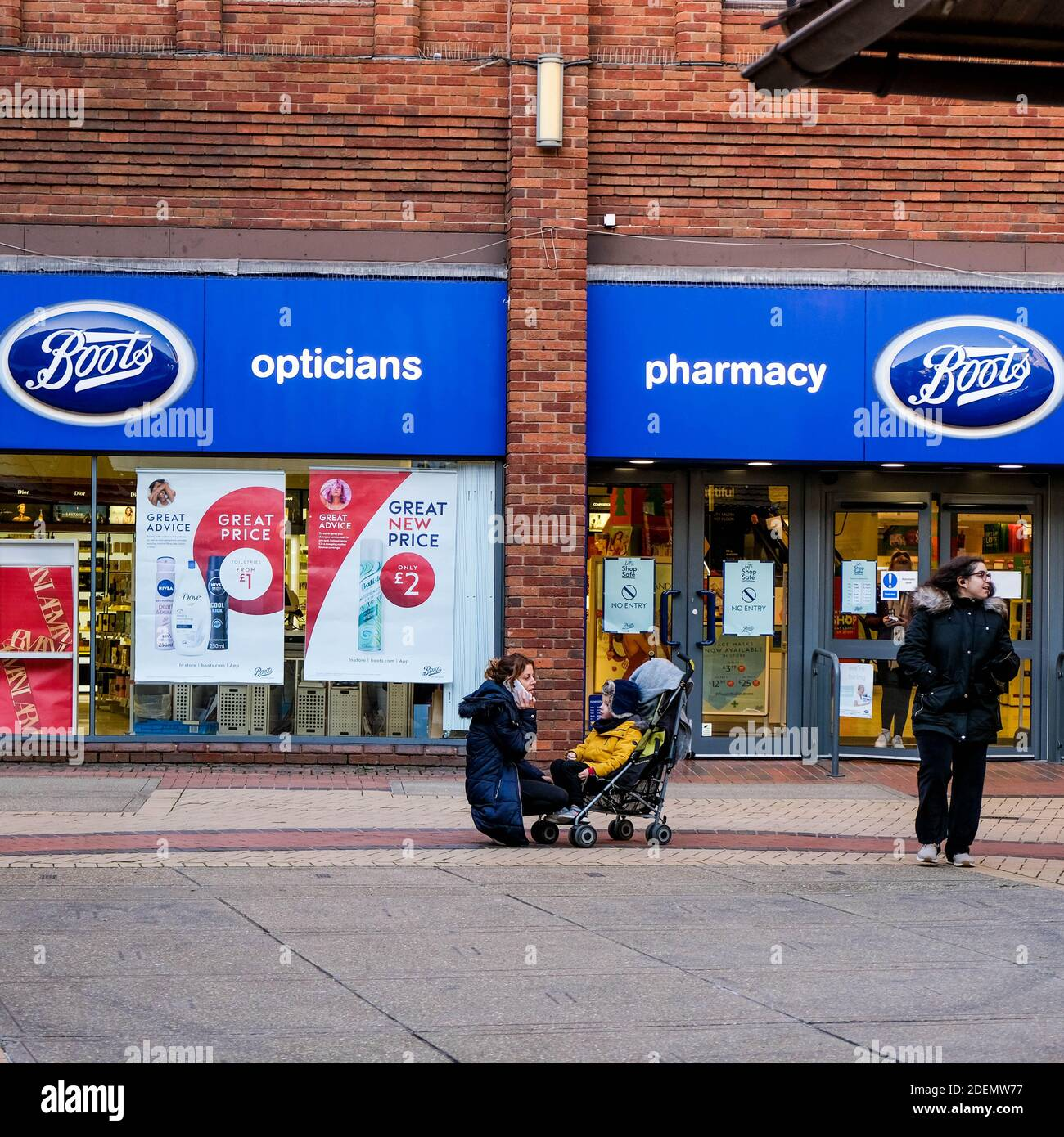 London UK, December 01 2020, Mother And Baby In A Pushchair Outside Boots Pharmacy Stock Photo