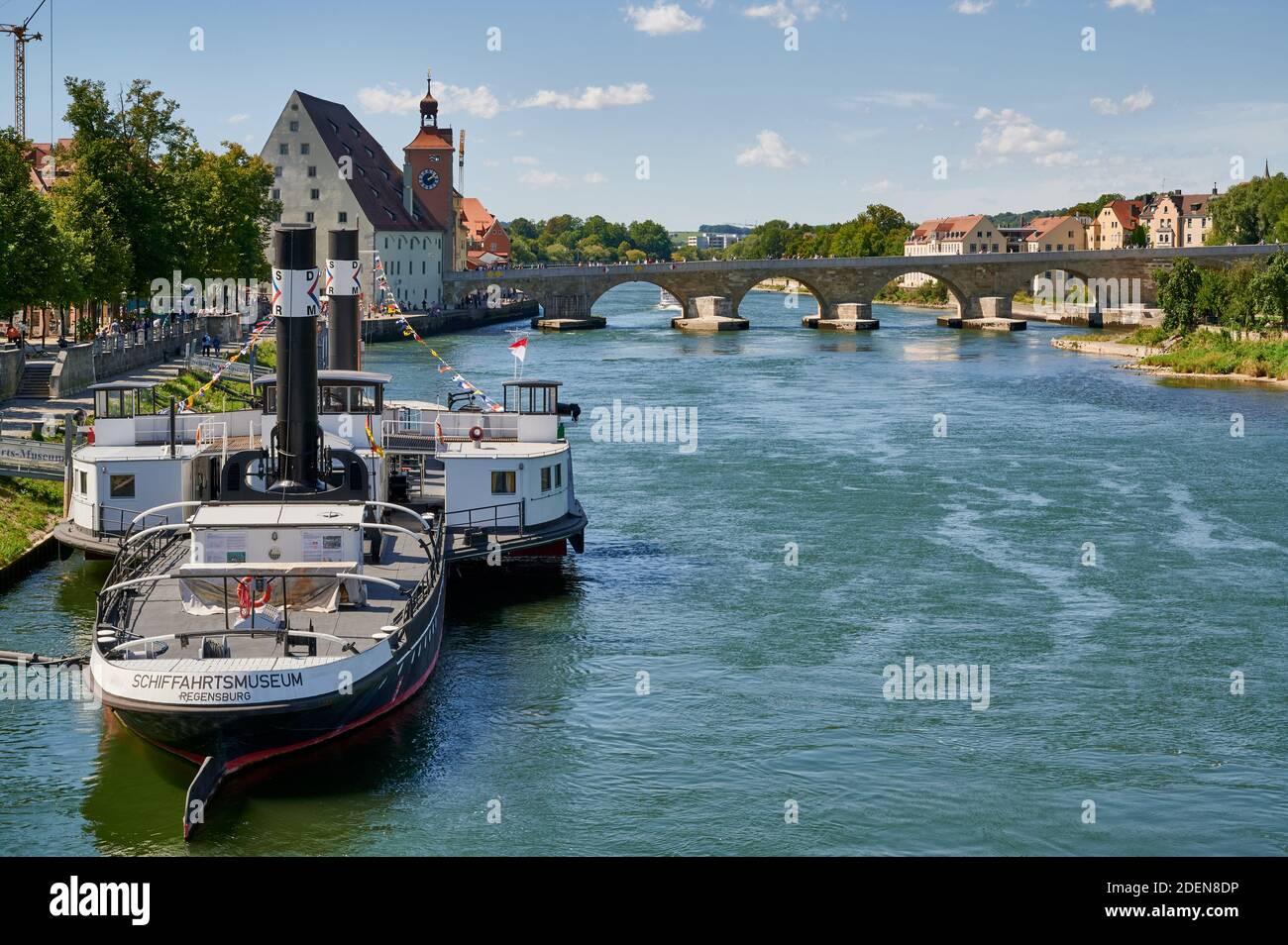 RUTHOF / ÉRSEKCSANÁD Ship Museum on River Danube and Steinerne Bruecke behind, Regensburg , Bavaria, Germany Stock Photo