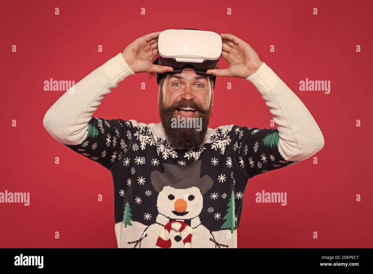 man winter sweater play game. indoor vs outdoor activity. Virtual reality. man wearing virtual reality goggles. xmas party. happy bearded hipster in vr glasses. interacting with a virtual environment Stock Photo