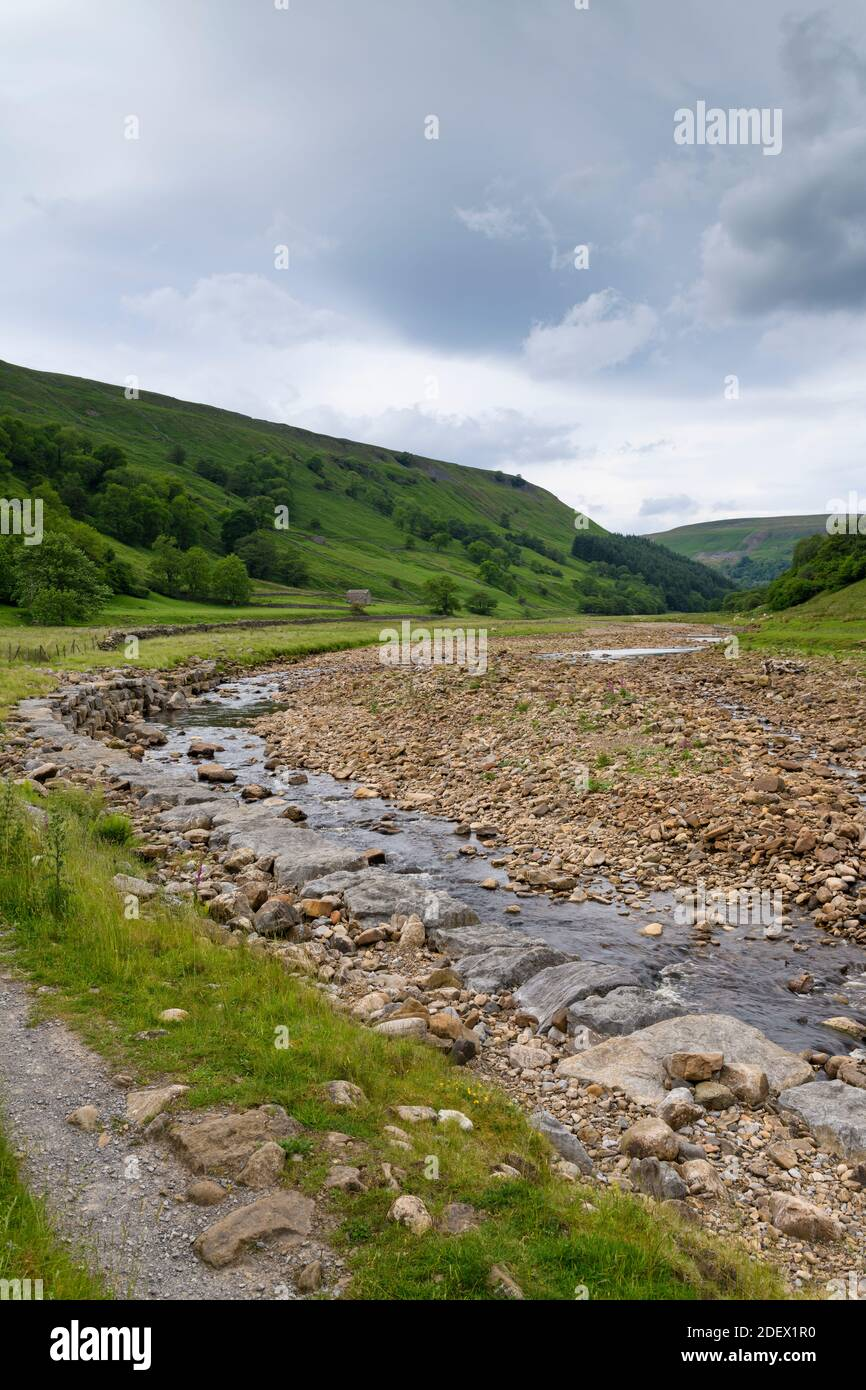 River Swale in scenic countryside valley (low shallow water channel in dry summer weather & riverbed rocks) - Swaledale, Yorkshire Dales, England, UK. Stock Photo