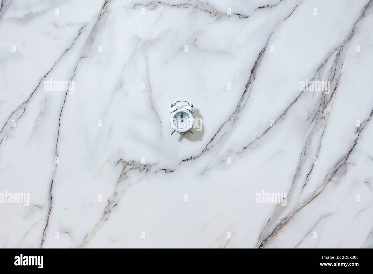 Top view of white alarm clock showing midnight or twelve on white Stock Photo
