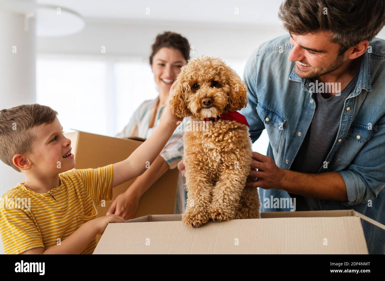 Happy family unpacking boxes in new home on moving day Stock Photo