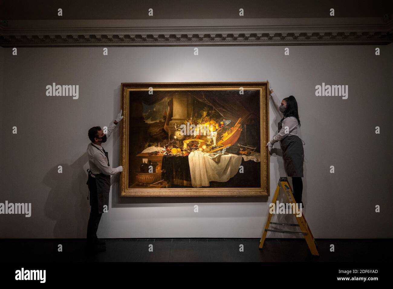 Gallery assistants adjust 'A banquet still life' by Jan Davidsz De Heem with an estimate of ??4-6 million, which is on show at Christie's saleroom in central London ahead of the auction house's forthcoming Classic Week sales. Stock Photo