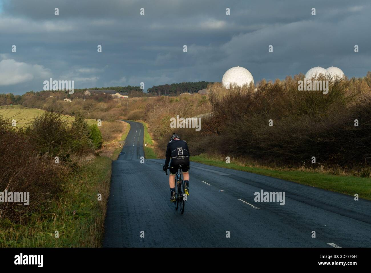 Cyclist cycling the B6461 past RAF Menwith Hill with white circular radomes of satellite ground station visible, North Yorkshire, England, UK Stock Photo