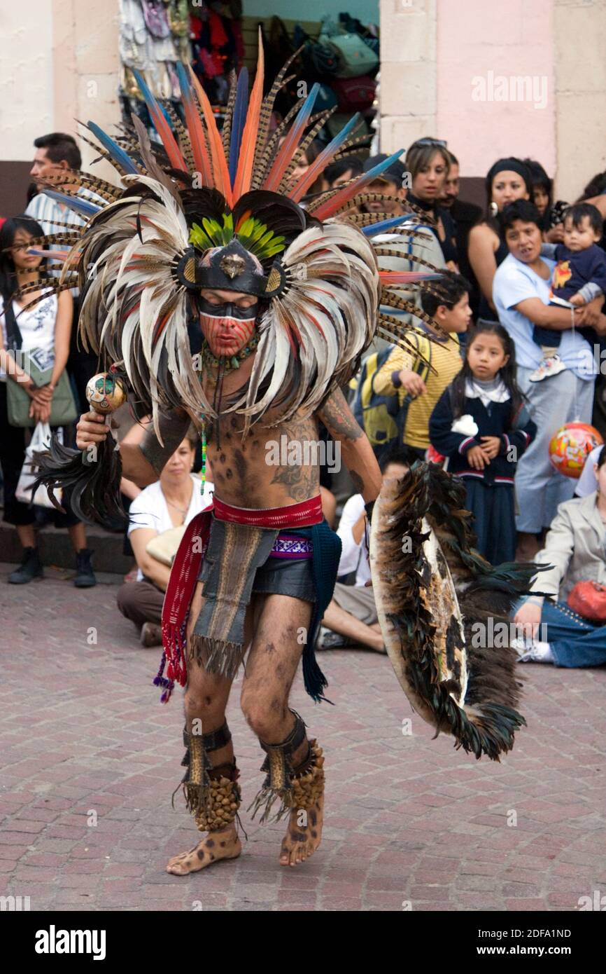An AZTEC DANCER dressed as a WARRIOR with headdress, rattle and shield during the CERVANTINO FESTIVAL  - GUANAJATO, MEXICO Stock Photo