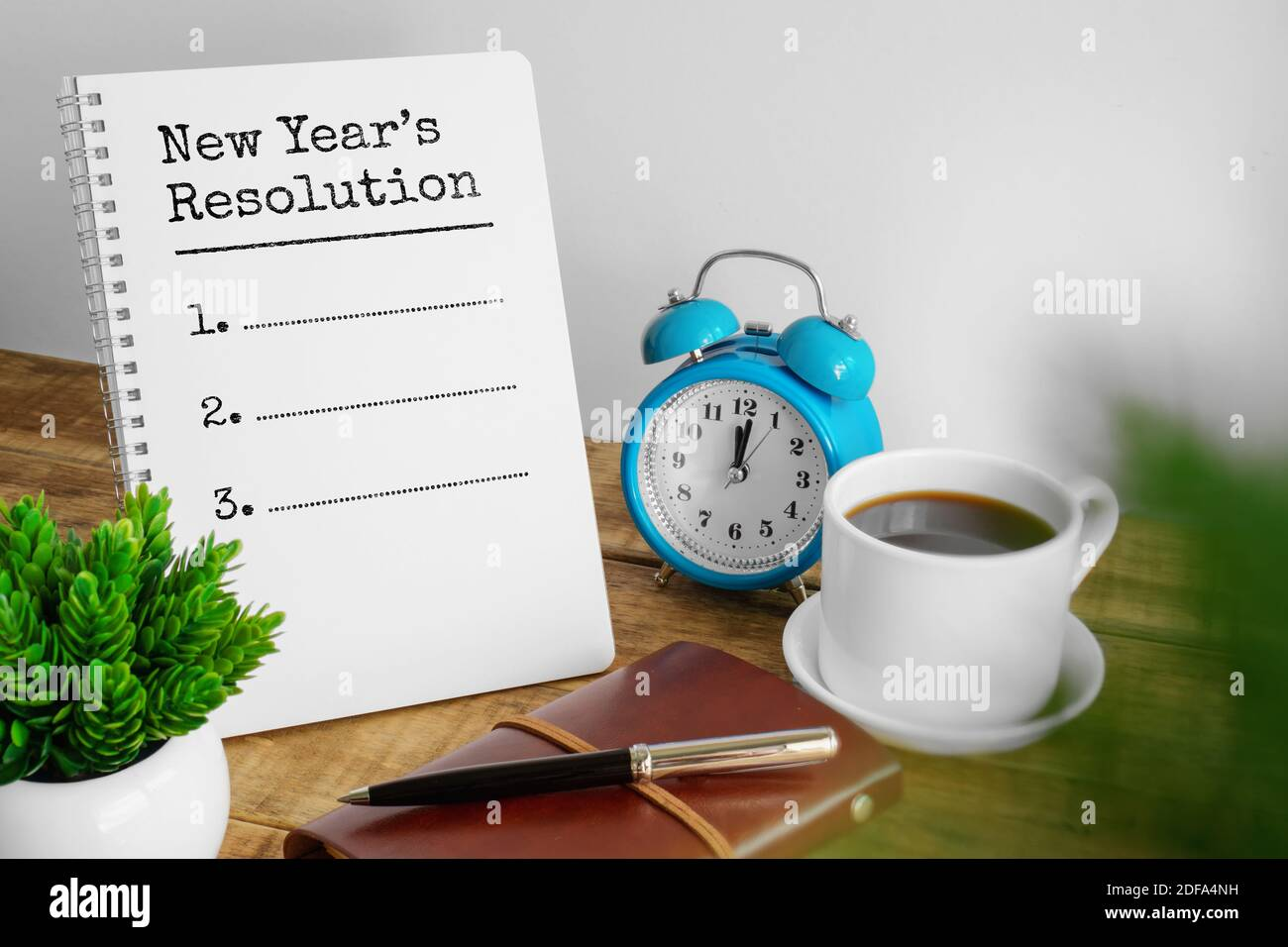 New year's resolution on notepad on rustic wood home office desk. Stock Photo