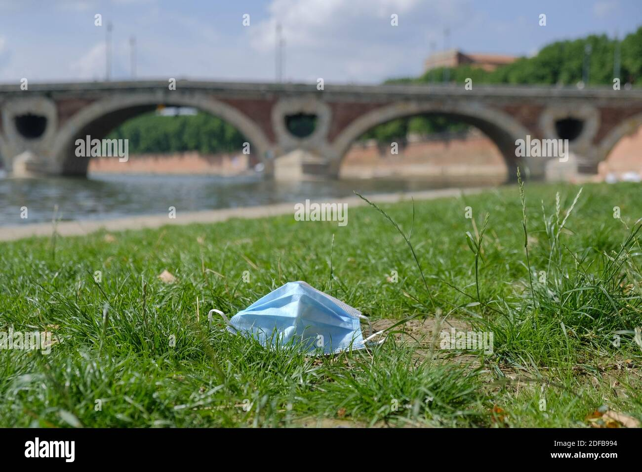 A protective face mask is seen discarded in the banks of the river Garonne in Toulouse, France, on June 27, 2020. As the use of masks and gloves sky-rocketed to protect the humanity from the coronavirus pandemic, their impact on environment also rose, with the worrying consumption of plastic and its disposal. Many fear the progress of eliminating single-use plastic is now being undone, as these protection tools are already being seen polluting the environment. Photo by Patrick Batard/ABACAPRESS.COM Stock Photo