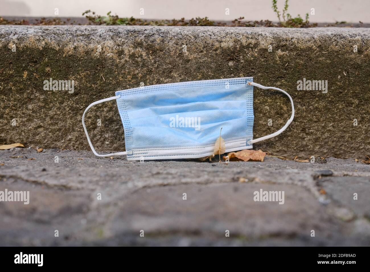 A protective face mask is seen discarded on the ground in Toulouse, France, on June 27, 2020. As the use of masks and gloves sky-rocketed to protect the humanity from the coronavirus pandemic, their impact on environment also rose, with the worrying consumption of plastic and its disposal. Many fear the progress of eliminating single-use plastic is now being undone, as these protection tools are already being seen polluting the environment. Photo by Patrick Batard/ABACAPRESS.COM Stock Photo