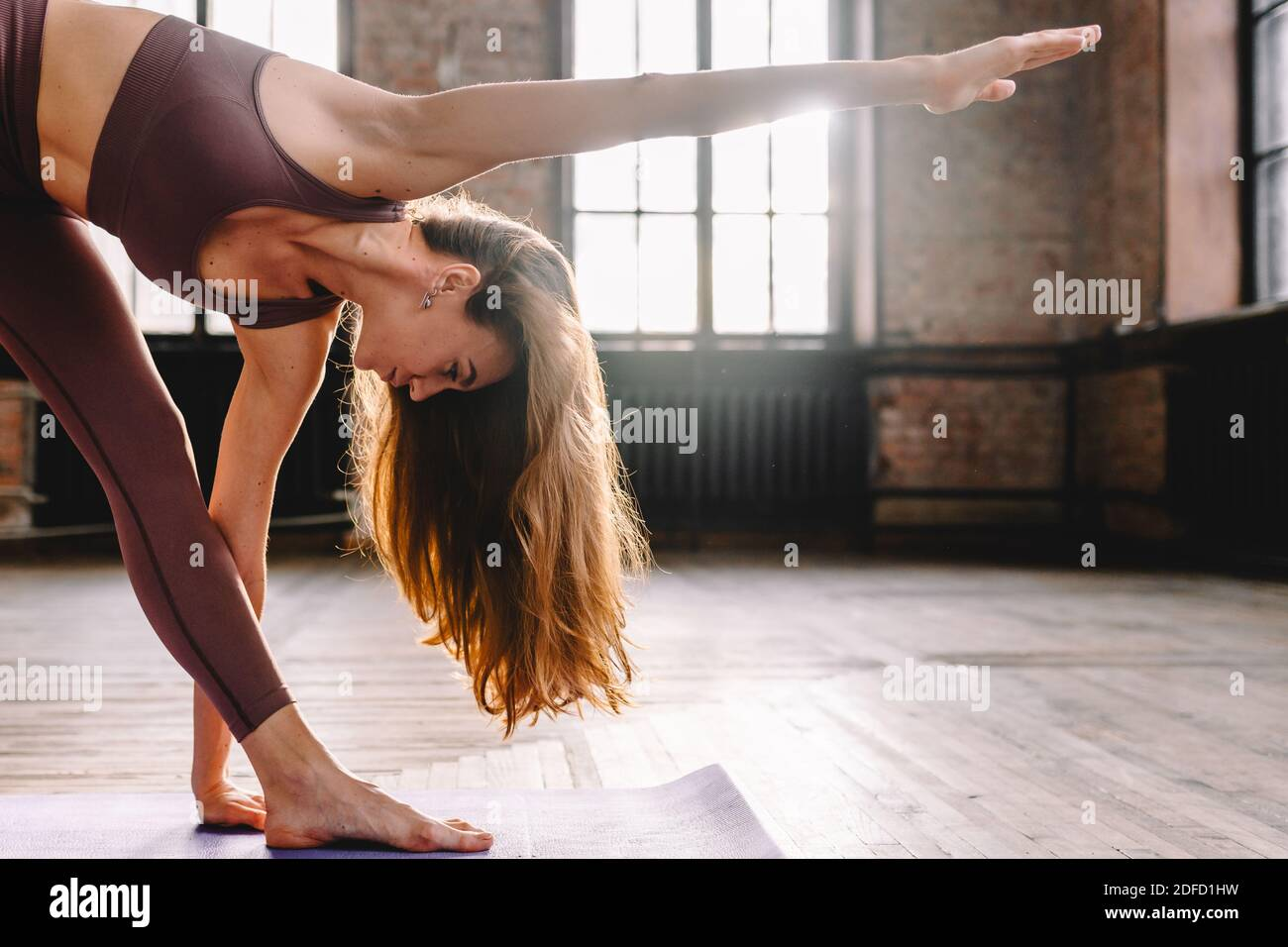 Young long haired woman do complex of stretching yoga asanas in loft style sunny class. Stock Photo